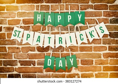 Happy St. Patrick's Day banner lettering on red, old orange brick wall background. Irish national colors greeting postcard template.