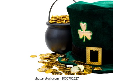 Happy St patrick's day concept with green leprechaun hat with shamrock, pot of gold and scattered golden coins isolated on white background with copy space and a clipping path included