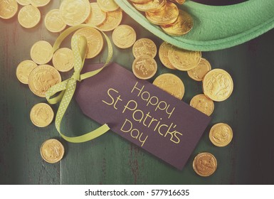 Happy St Patricks Day leprechaun hat with gold chocolate coins on vintage style green wood background, with applied retro style faded filters.