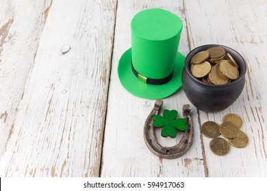 Happy St Patricks Day leprechaun hat with gold coins and lucky charms on vintage style white wood background. Top view