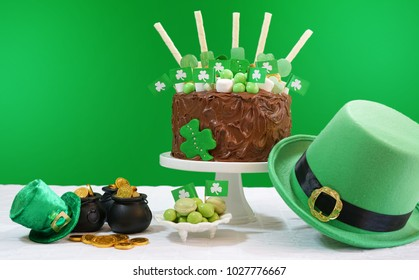 Happy St Patrick's Day, March 17, green and white party table with showstopper chocolate cake decorated with candy, cookies and shamrock flags, with lens flare.