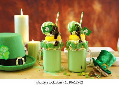 Happy St Patrick's Day on-trend holiday freak shakes milkshakes decorated with candy and lollipops, preparation.