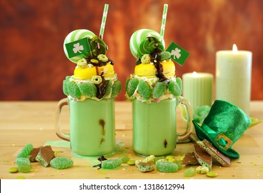 Happy St Patrick's Day on-trend holiday freak shakes milkshakes decorated with candy and lollipops.