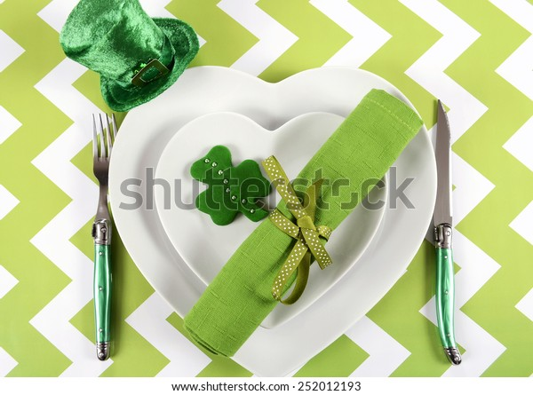 Happy St Patricks Day table place setting with heart shape plates, shamrock cookie and leprechaun hat on green and white chevron stripe table.