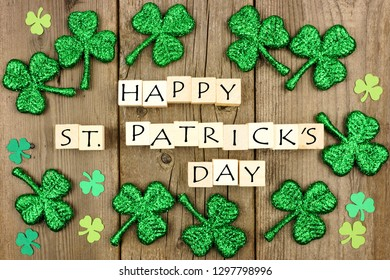 Happy St Patricks Day wooden blocks with shamrock decor on a rustic wood background