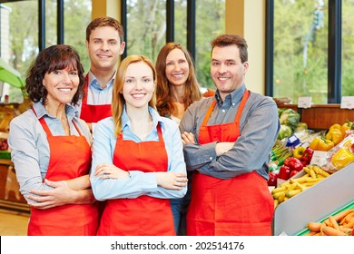 Happy staff team with men and women in a supermarket