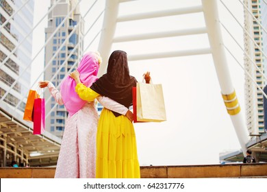 Happy of standing two woman Muslim, woman holding shopping bags in the city background,vintage tone