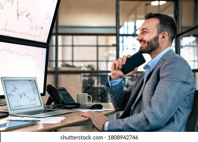 Happy stock broker looking at display, smiling wide, holding smartphone and analyzing dynamic on forex charts, working in office
