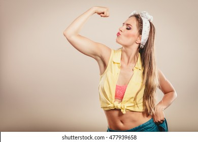 Happy strong pretty pin up girl with hairband bow showing off muscles. Young gorgeous retro woman in studio.