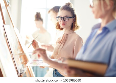Happy student of arts school looking at camera between her groupmates and teacher painting on easels