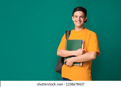 Happy student with books and backpack over turquoise background, copy space