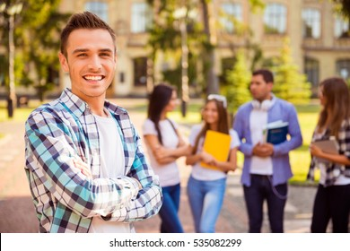 Happy student and crossing hands  while standing on background of university and friends