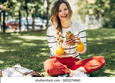 Happy student female sitting on the green grass at the college campus on a sunny day, have lunch and studying outdoors. A smiling young woman takes a rest eating fast food and learning in the park.