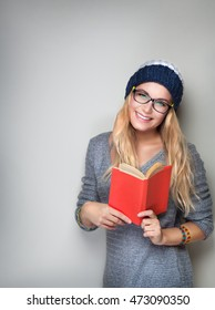 Happy student girl with book in hands wearing stylish hat and glasses isolated on gray background, enrollee of university