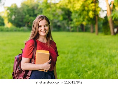 Happy student girl with notes and backpack. Entering the university, starting school in September