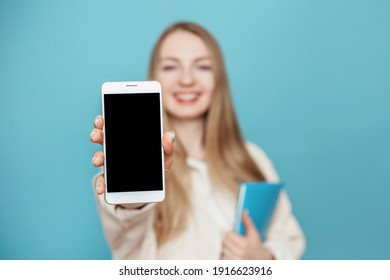 Happy student girl shows a blank screen of a mobile phone at the camera and smiles, girl in blur. Isolated on a blue background in the studio. Mockup