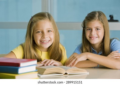 Happy student girls with books, studying
