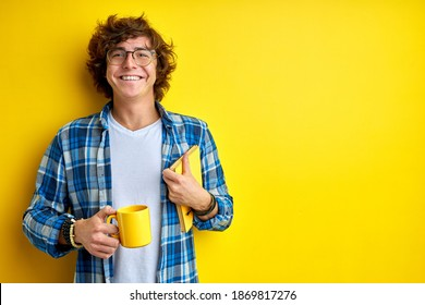 happy student guy is ready to study, stand with cup of tea and book in the morning, begin day with hot tea, smiling