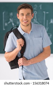 Happy student. Handsome young men holding backpack and smiling while standing in front of the blackboard