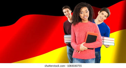Happy student holding books on german flag