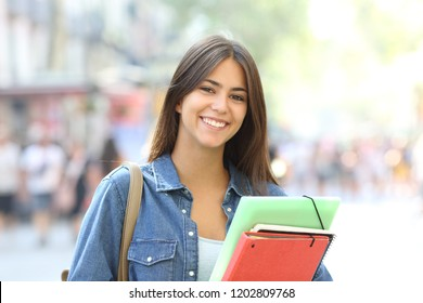 Happy student holding folders poses looking at camera in the street