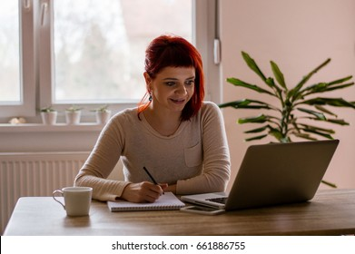 Happy student learning on line and taking notes in a notepad