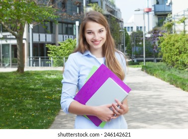 Happy, student with long blond hair on campus