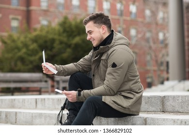Happy student man reads approval letter after college exams or job offer sitting in campus