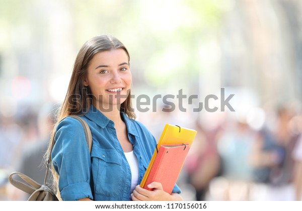 Happy student posing smiling and looking at camera in the street