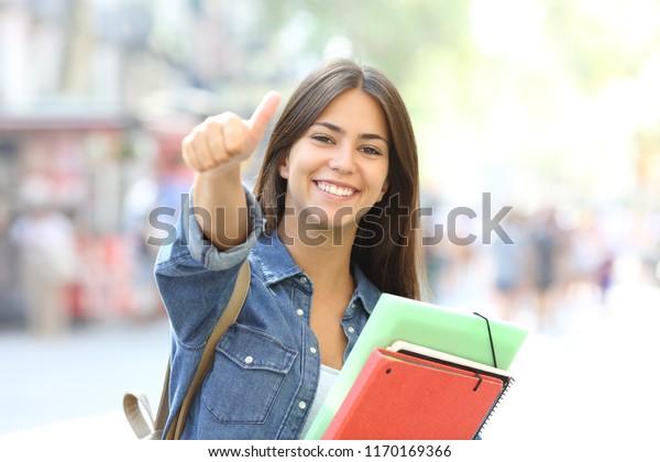 felice studente in posa con pollici in su guardando a si in il strada