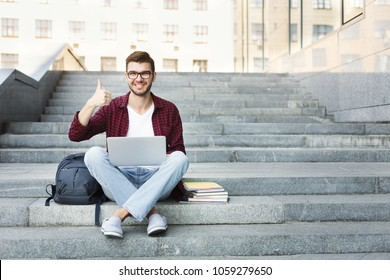 Happy student sitting on the stairs showing thumb up working on laptop, in the university campus. Technology, education and remote working concept, copy space