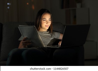 Happy student studying online in the night sitting on a couch in the living room at home