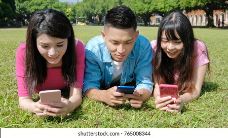 happy student use phone and play mobile game on the lawn
