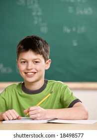 Happy student writing in notebook in school classroom