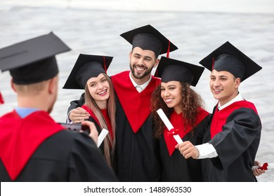 Happy students in bachelor robes and with diplomas outdoors