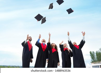 Happy students in bachelor robes throwing graduation hats outdoors