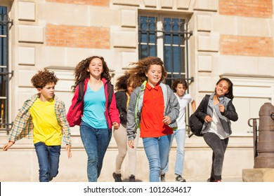 Happy students with backpacks running outdoors