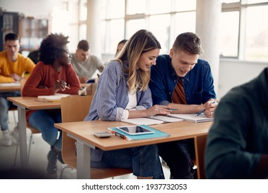 Happy students cooperating while studying lecture during class at university classroom.