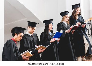 happy students in graduation gowns holding diplomas and reading books