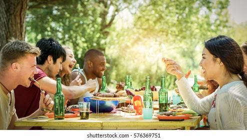 Happy students having barbecue on summer day in backyard home garden - Young cheerful people eating tasty bbq dinner - Concept about positive mood with friends - Warm filter