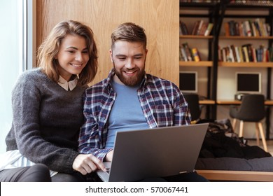 Happy students with laptop computer networking in library while sitting on the windowsill