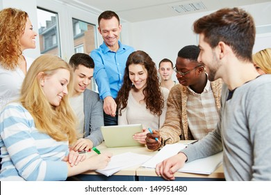 Happy students learning with teacher in university class