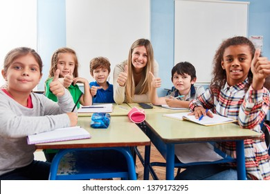 Happy students of a multicultural elementary school keep their fingers crossed
