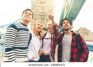 Happy students on Tower Bridge in London during school trip - Multiracial group of teenagers best friends enjoying time together visiting the city - Lifestyle and tourism in London