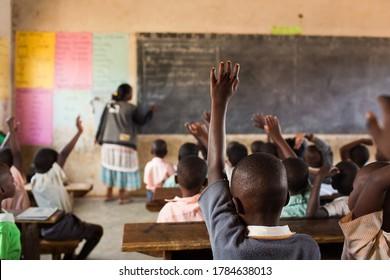 Glückliche Schüler an einer Schule in Uganda, Afrika.  Schüler heben sich die Hände.
