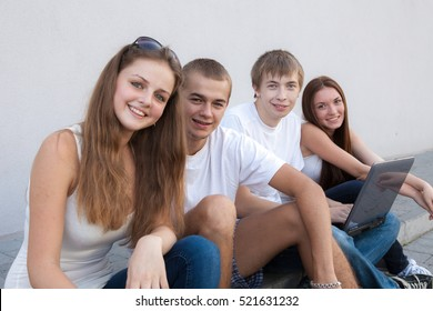 Happy students sitting in street