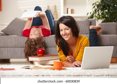 Happy students studying at home in living room with books and laptop, looking at camera smiling.?