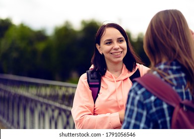 Happy students talking after studies. Cheerful young woman with backpack smiling and talking with female friend while standing on bridge after university studies