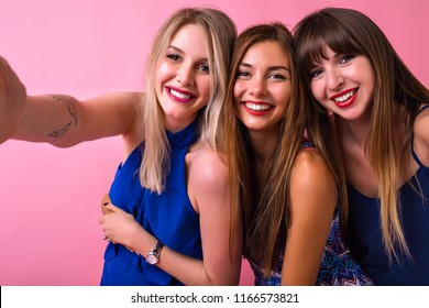 Happy stunning funny three sisters best friends girls making selfie at studio, pink background, long hairs natural make up and amazing smiles, ready for party.