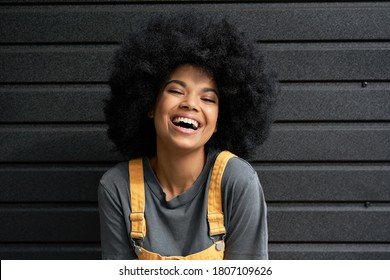 Happy stylish African American young woman wearing yellow trendy sundress with Afro hair looking at camera laughing on black background. Smiling mixed race hipster headshot closeup portrait.